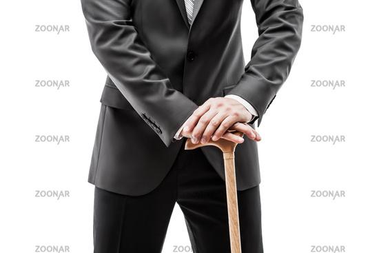 Businessman in black suit holding walking cane stick
