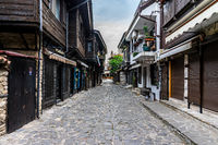 Beautiful and narrow street with restaurants, cafes and shops of the ancient seaside town.