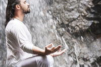 Wellness yoga meditation concept. Young man sitting in lotus position on the rock under tropical waterfall.