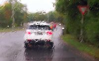 Driving a car in the rain and storm in heavy traffic. View through a windshield.