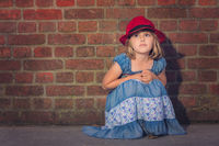 Little girl with a red hat looking sad