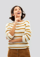 happy woman in striped pullover looking up