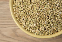 Natural fresh green buckwheat in ceramic bowl on wooden background. Top view.