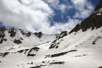 High mountains with avalanche tracks, snowy plateau and cloudy sunlit sky