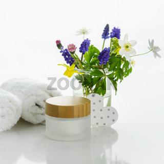 Handtücher mit Herz neben einer Cremedose vor weißem Hintergrund und Blumen in einer Vase.