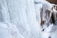 Frozen ice on rocks from a waterfall in the mountains
