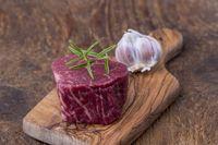 rohes Steak auf dunklem Holz