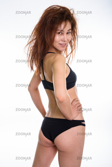 Studio shot of young happy Asian woman smiling while looking bac