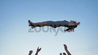 Friends of schoolchildren throw up a girl at sunset.