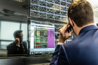 Stock broker trading online, talking on mobile phone.