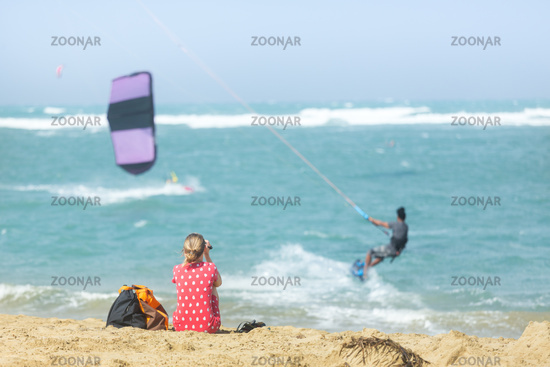 Girl sitting on sandy beach watching kite surfer in the sea.