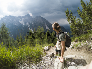 Man on the hill watching wonderful scenery in mountains during summer colorful sunset in Italy Alps. Travel Lifestyle hiking concept summer vacations outdoor.