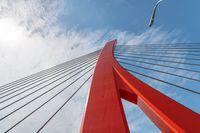 Red cable bridge against blue sky