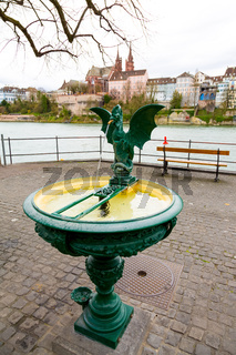 Basilisk fountain with view of Basel old Town and Rhine river, Switzerland