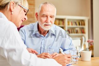 Ärztin stellt ein Rezept aus für Senior Mann