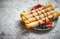 Plate of delicious crepes roll with fresh fruits and chocolate