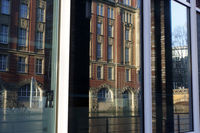 Old building on Alsterfleet reflected in windows of a modern office complex