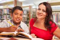 Hispanic Young Boy and Famle Adult Studying At Library