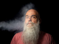 bearded man gets smoke in his face portrait