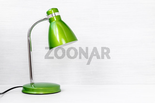Green lamp on wooden desk