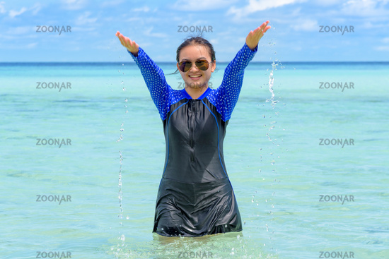 Happy asian teen girl play splashing water in the sea