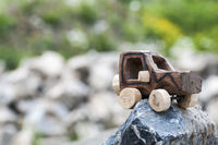 Wooden SUV, toy car in an extreme landscape.