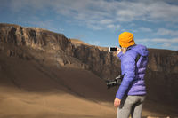 Portrait from the back of a traveling girl in a down jacket with a cap taking pictures of an epic landscape with rocks on her smartphone
