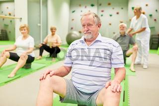 Gruppe Senioren macht Krankengymnastik mit Anleitung