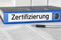 A blue folder with the label Certification - Zertifizierung (German)