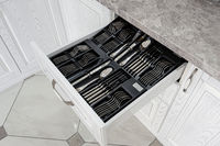 drawer with silver cutlery in modern white kitchen