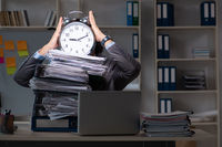 Young male employee working late at office