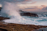 Waves splash high onto the coastal rock shelf at sunrise