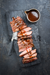 Traditional American barbecue dry aged flank steak sliced with hot chili sauce as top view on an old carbonized board