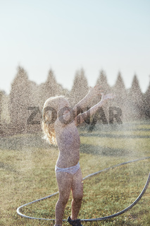 Little girl enjoying a cool water sprayed by her mother