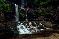 Woman basking in lush mountain waterfall