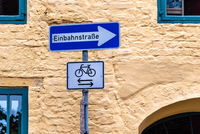 One way street sign in Germany against urban background.
