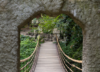 Walk through the park forest arch gate to a hanging wooden bridge among the greenery