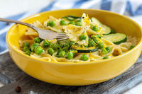 Farfalle pasta with zucchini and green peas.