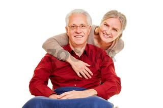 Alte Frau umarmt Senior Mann im Rollstuhl