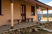 Happy relaxed female on verandah of old timber home in the rural countryside