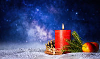 Candle with christmas decoration in front of starry sky