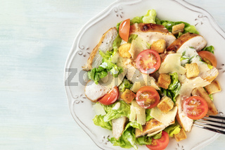 A close-up of a chicken Caesar salad, shot from the top with a place for text