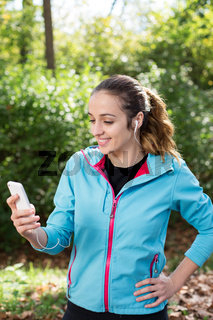 Running woman. Female runner relaxing after jogging outdoor workout. Beautiful fit girl using her mobile phone.