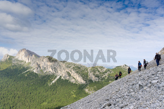 panorama of a group of mountain climbers hiking up a mountain side to a hard climbing route