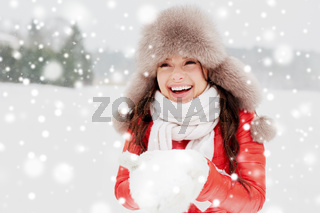 happy woman with snow in winter fur hat outdoors