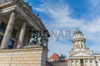 Berlin, Germany - September 23, 2018: Upwards and horizontal view the Konzerthaus building in Berlin, Germany, with beige and green colors and a blue sky with dispersed clouds in the background