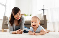 sweet little asian baby boy with mother at home