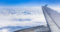 snow covered mountain range seen from aircraft window