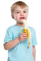 Kind Banane Obst Frucht essen gesunde Ernährung blond Hochformat isoliert Freisteller freigestellt