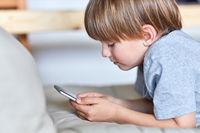 Kleiner Junge schaut auf sein Smartphone